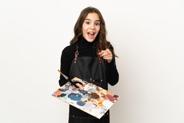 Menina artista segurando uma paleta isolada no fundo branco surpresa e apontando para a frente