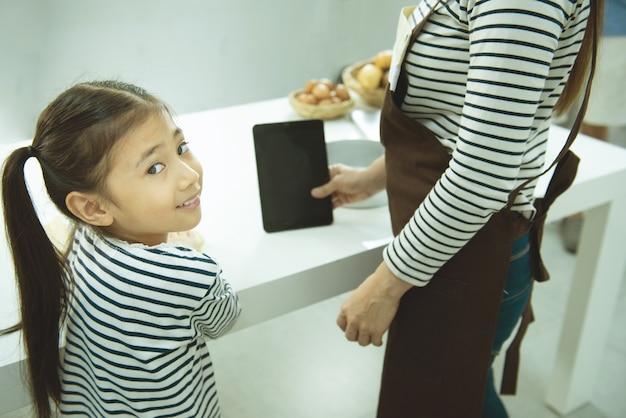 Menina asain olhar para a câmera enquanto cozinha a farinha na mesa com a mãe segurar o tablet.