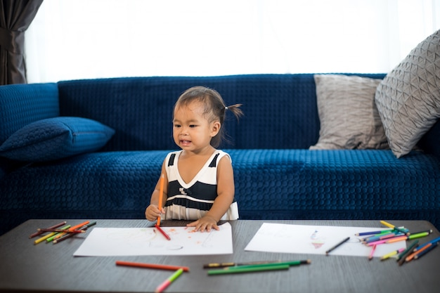 Menina ásia, desenho fammily em uma grande folha de papel branco
