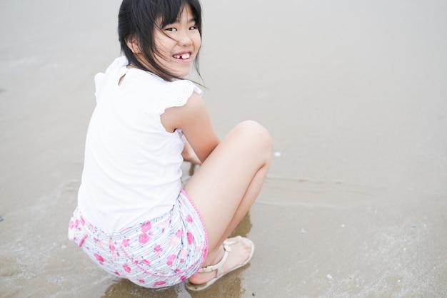 Menina ásia, tocando, praia, dela, sorrizo
