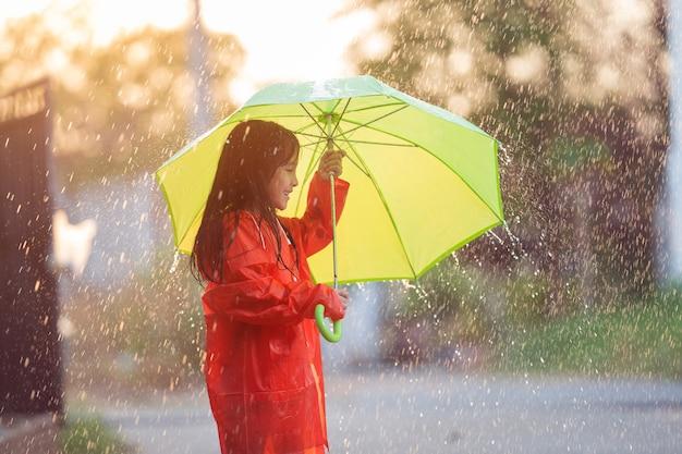 Menina asiática abre um guarda-chuva em um dia chuvoso.