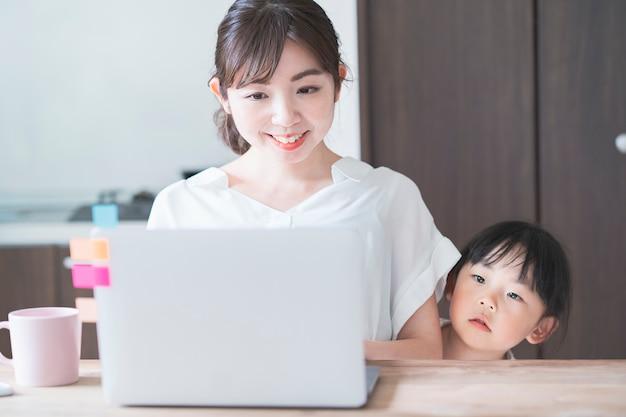 Menina asiática aconchegando-se até a mãe