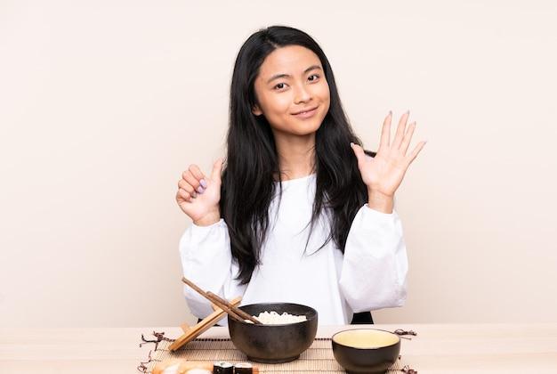 Menina asiática adolescente comendo comida asiática isolada em um fundo bege, contando seis com os dedos