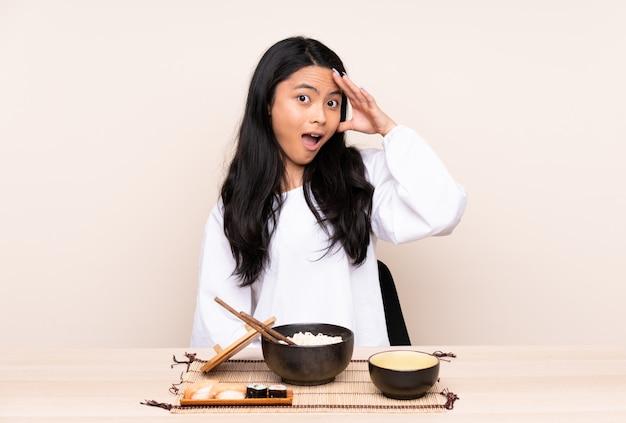 Menina asiática adolescente comendo comida asiática na parede bege acaba de perceber algo e tem a intenção de solução