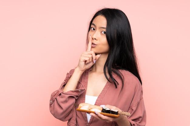Menina asiática adolescente comendo sushi isolado em rosa fazendo gesto de silêncio