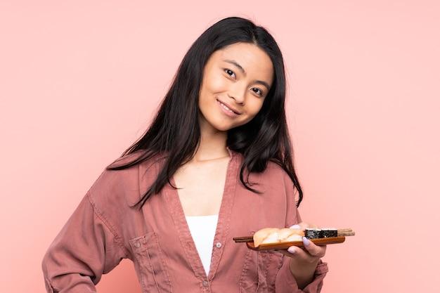 Menina asiática adolescente comendo sushi isolado em um fundo rosa rindo