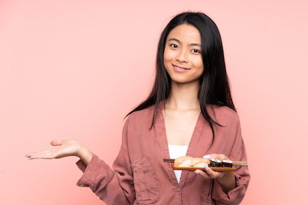 Menina asiática adolescente comendo sushi isolado na rosa segurando uma cópia do espaço imaginário na palma da mão