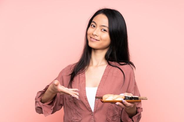 Menina asiática adolescente comendo sushi isolado no rosa estendendo as mãos para o lado para convidar para vir