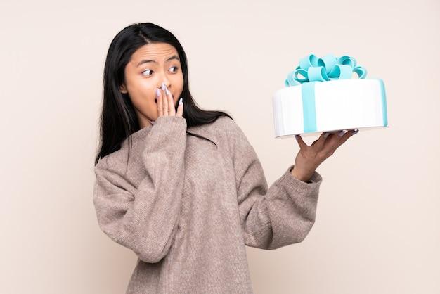 Menina asiática adolescente segurando um grande bolo isolado em bege com expressão facial surpresa e chocada