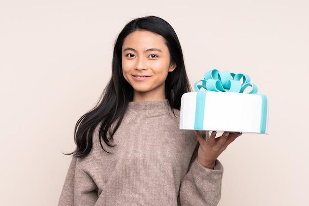 Menina asiática adolescente segurando um grande bolo