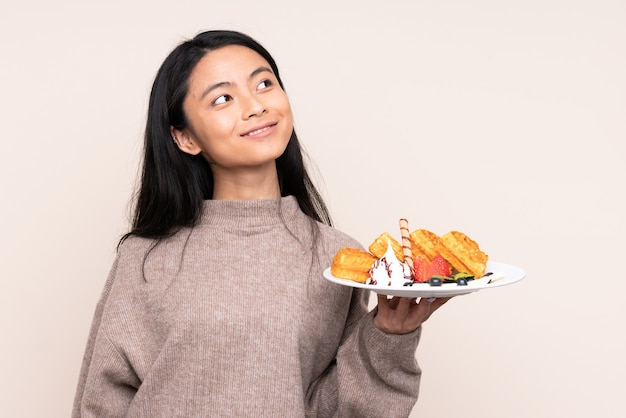 Menina asiática adolescente segurando waffles isolados em bege, olhando para cima enquanto sorri