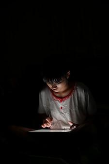 Menina asiática adolescente usando tablet desenho enquanto estava deitado na cama