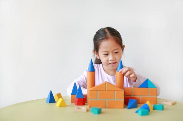 Menina asiática adorável que joga um brinquedo colorido do bloco de madeira na tabela.