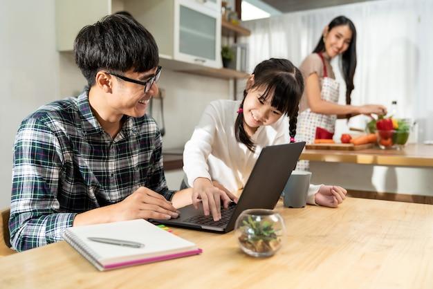 Menina asiática ajudando o pai a trabalhar com um laptop enquanto a mãe cozinha