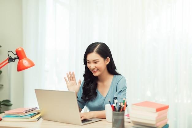 Menina asiática alegre positiva com transmissão de videochamada online conhecer blogueiros dizer oi onda mão sentar mesa usar laptop dentro de casa
