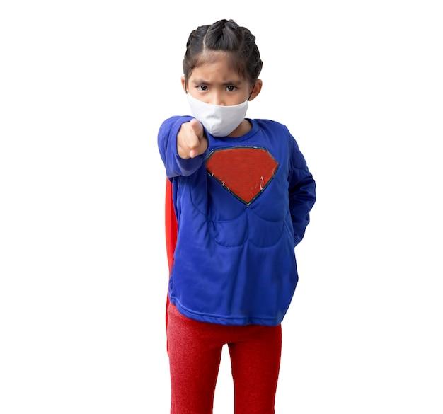 Menina asiática aponta para a câmera fantasiada de herói e usando máscara médica em fundo branco