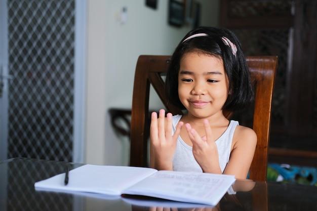 Menina asiática aprendendo a contar com os dedos