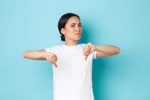 Menina asiática arrogante, cética e decepcionada compartilha sua opinião negativa, fazendo caretas e balançando a cabeça em desaprovação, deixando comentários ruins, mostrando o polegar para baixo descontente, parede azul.
