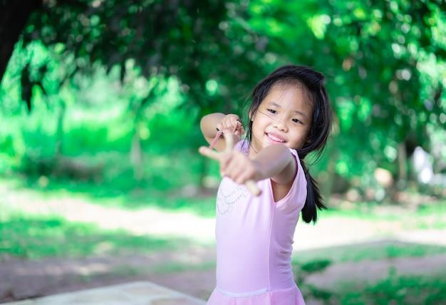 Menina asiática atirando com o estilingue de madeira contra uma árvore verde, lazer ativo para crianças.