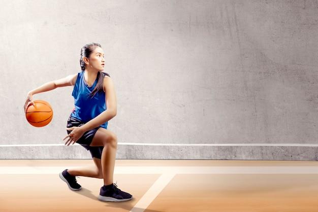 Menina asiática atraente no uniforme de esporte azul no pivô de basquete move-se na quadra de basquete