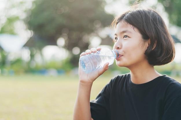 Menina asiática beber água fresca de garrafa de plástico com fundo por do sol