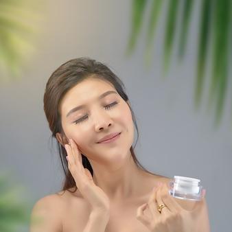 Menina asiática bonita feliz com a pele fresca com fundo da luz solar.