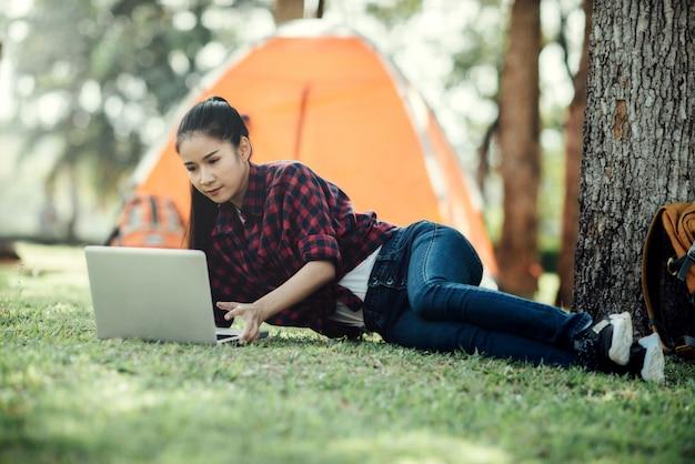 Menina asiática bonita nova que usa o portátil.