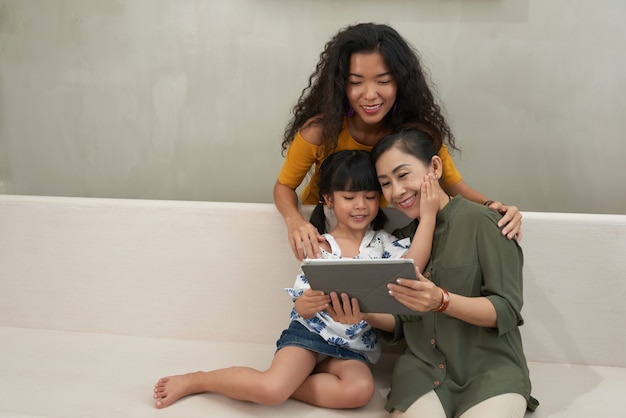Menina asiática bonita positiva tocando a bochecha da avó enquanto assistia ao desenho animado com ela e sua mãe em casa
