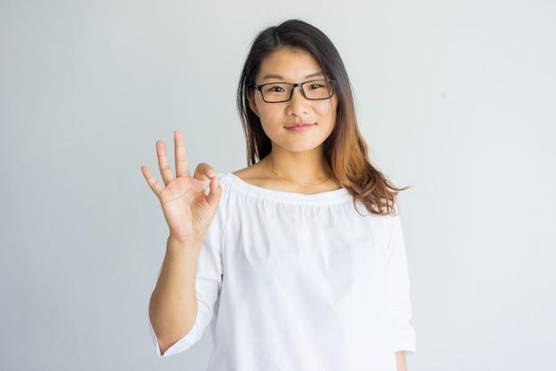 Menina asiática bonita satisfeita com o cabelo destacado que faz o sinal aprovado como o símbolo da aprovação.
