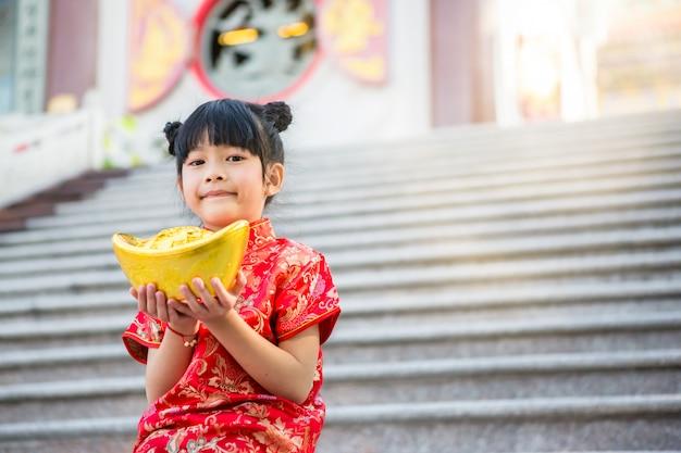 Menina asiática bonita usar cheongsam vermelho e segurando o lingote de ouro chinês na frente dos degraus de mármore do belo templo chinês para o ano novo chinês