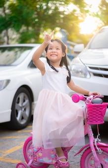 Menina asiática bonitinha andando de bicicleta com a luz solar, crianças esporte e estilo de vida ativo