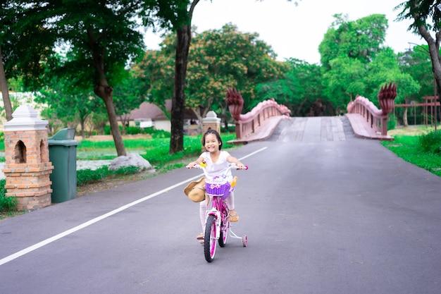 Menina asiática bonitinha andando de bicicleta para se exercitar no parque, esportes infantis e estilo de vida ativo