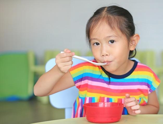 Menina asiática bonitinha comer cereais com flocos de milho e leite em cima da mesa