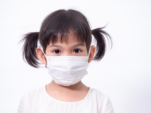 Menina asiática bonitinha de 4 anos de idade, vestindo uma máscara higiênica para proteger a propagação da gripe resfriada do vírus de corona covid-19 ou poluição na parede branca.