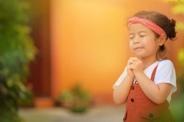 Menina asiática bonitinha fechou os olhos e rezando de manhã. mão asiática pequena da menina que reza, mãos dobradas no conceito da oração para a fé, a espiritualidade e a religião.
