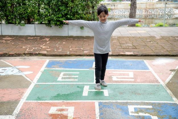 Menina asiática bonitinha jogando amarelinha ao ar livre. divertido jogo de atividades para crianças no playground do lado de fora. esporte de rua de quintal de verão para crianças. estilo de vida de infância feliz.