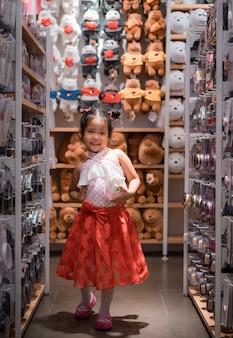 Menina asiática bonitinha no vestido com uma boneca na loja