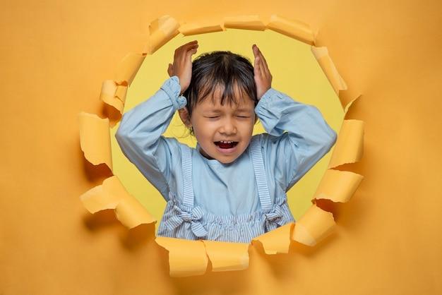 Menina asiática bonitinha posa através do buraco de papel amarelo rasgado, segurando a cabeça com as mãos
