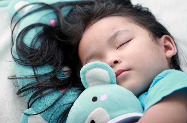 Menina asiática bonitinha sono e abraço ursinho de pelúcia