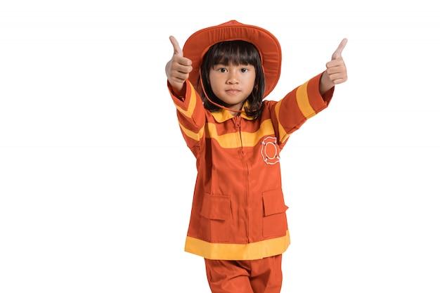 Menina asiática bonitinha vestindo um uniforme de bombeiro