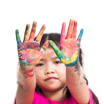 Menina asiática bonito com as mãos pintadas na pintura colorida no fundo branco