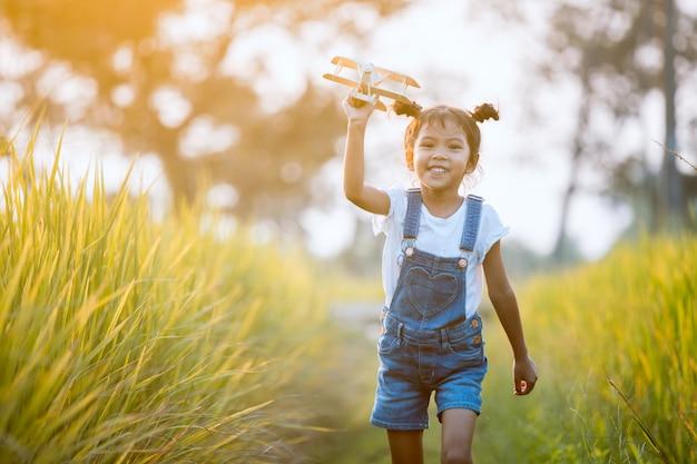 Menina asiática bonito da criança correndo e brincando com o avião de brinquedo de madeira no campo