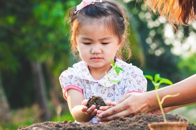 Menina asiática bonito da criança e pai que plantam mudas novas no solo preto junto