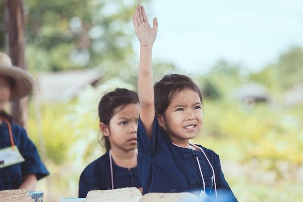 Menina asiática bonito da criança levantando a mão no ar para responder à pergunta na sala de aula