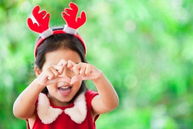 Menina asiática bonito da criança no vestido do natal que faz a forma do coração com mãos