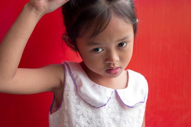 Menina asiática bonito da criança pequena no fundo vermelho.