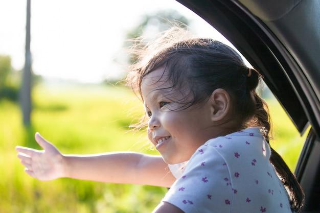 Menina asiática bonito da criança pequena que sorri e que tem o divertimento para viajar pelo carro.