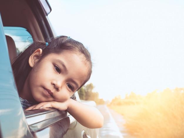 Menina asiática bonito da criança pequena que viaja pelo carro e que olha para fora da janela de carro no campo