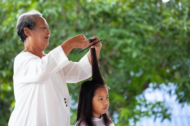 Menina asiática bonito da criança que corta o cabelo pela avó em casa