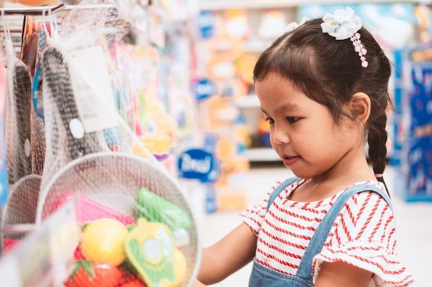 Menina asiática bonito da criança que escolhe o brinquedo e que compra no supermercado